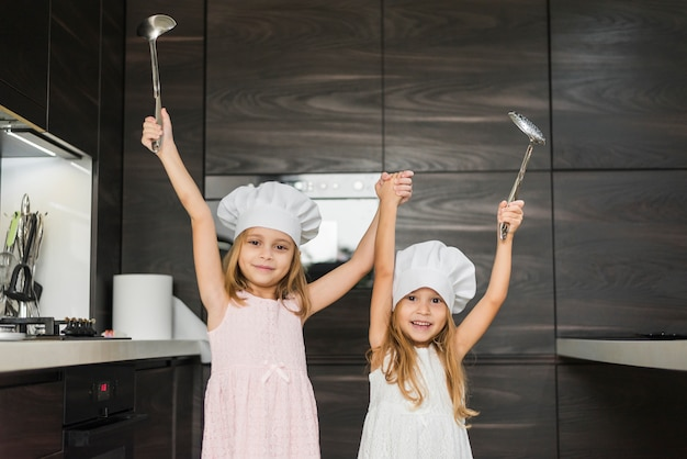 Smiling siblings with raised hands in kitchen holding ladle