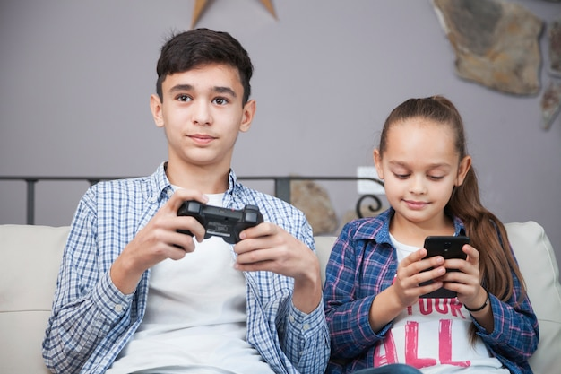 Smiling siblings with smartphone and controller