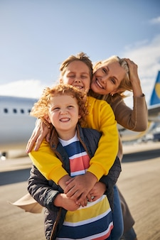 Smiling siblings with their mother close to an aircraft