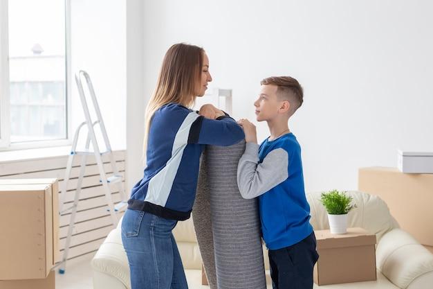 웃는 미혼모와 매력적인 아들이 새 아파트에 깔고 자하는 새 거실에 접힌 카펫을 들고있다