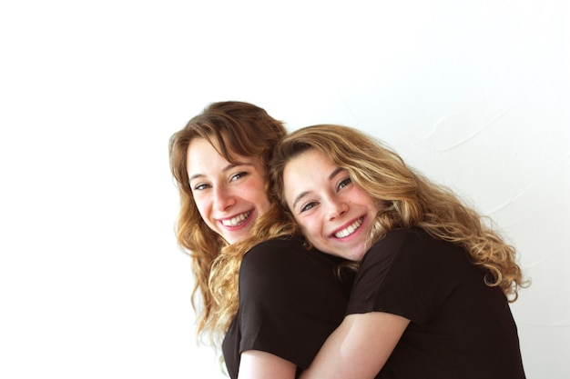 Smiling sister embracing each other against white background