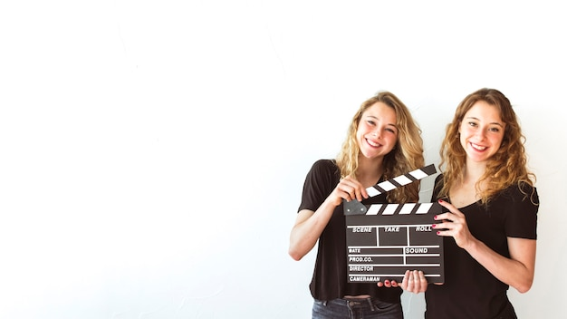 Smiling sister holding clapperboard against white background