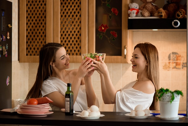 Smiling sisters preparing dinner together in the kitchen