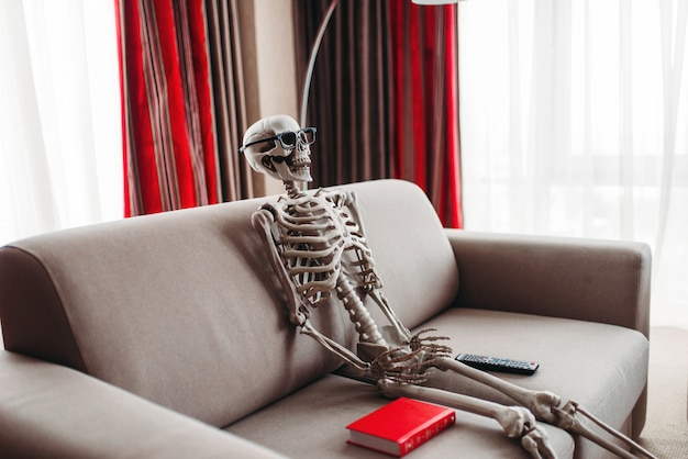 Smiling skeleton in glasses is sitting on couch between book and tv remote control, window and red curtains