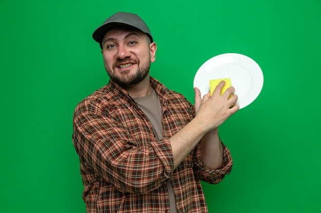 Smiling slavic cleaner man cleaning plate with sponge