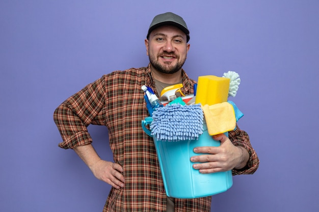 Sorridente addetto alle pulizie slavo che tiene in mano l'attrezzatura per la pulizia e