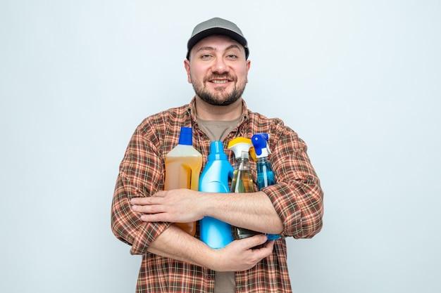 Sorridente addetto alle pulizie slavo che tiene in mano spray e liquidi per la pulizia