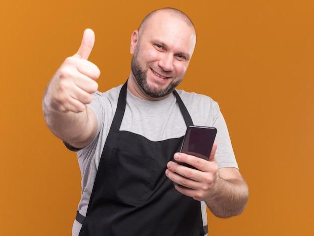 주황색 벽에 고립 된 엄지 손가락을 보여주는 제복을 입은 전화를 들고 슬라브 중년 남성 이발사 미소