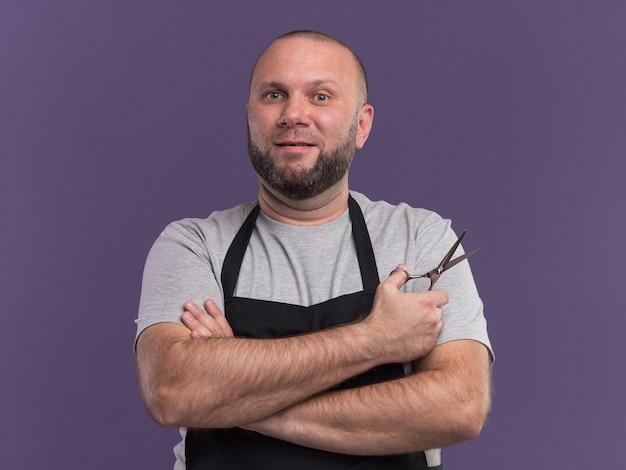 紫色の壁に分離された手を交差するはさみを保持している制服を着たスラブの中年男性床屋の笑顔