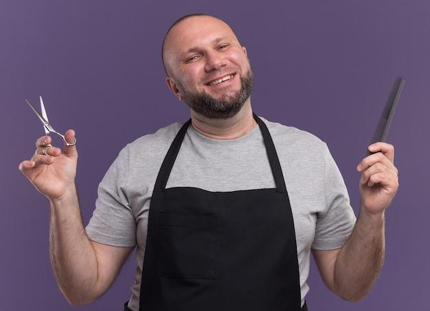 Улыбающийся славянский парикмахер средних лет в униформе держит ножницы с расческой на фиолетовой стене