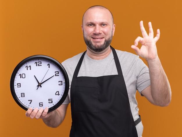 Barbiere maschio di mezza età slavo sorridente in orologio da parete della tenuta uniforme che mostra gesto giusto isolato sulla parete arancio