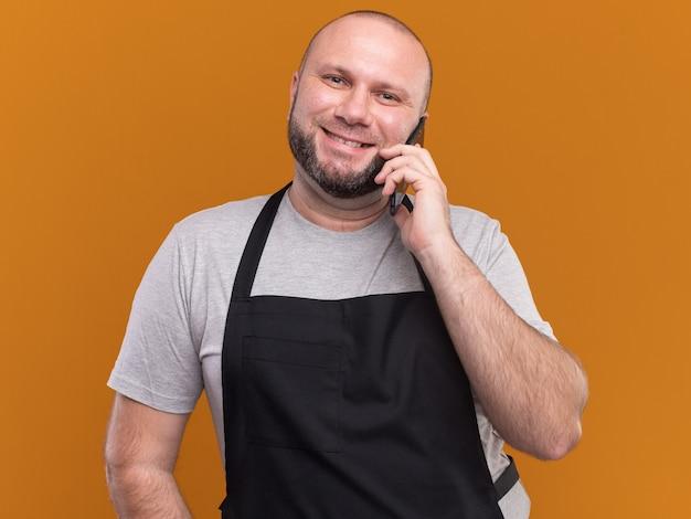 Sorridente barbiere maschio di mezza età slavo in uniforme parla al telefono isolato sulla parete arancione