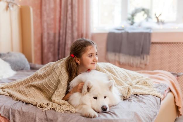 Улыбающаяся сонная милая маленькая девочка обнимает большую самоедскую собаку дома