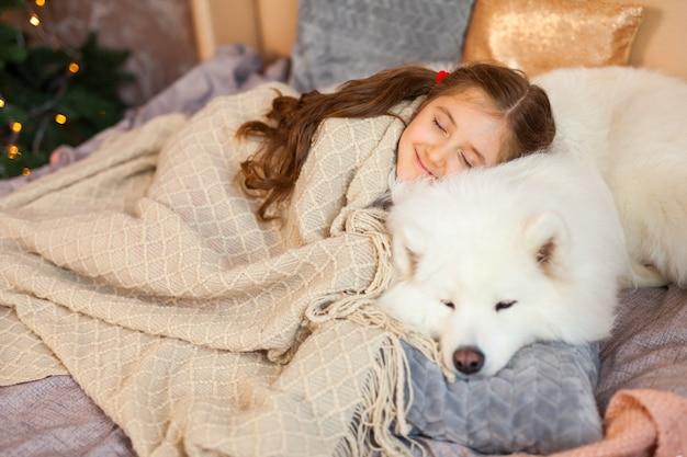 Улыбающаяся сонная милая маленькая девочка обнимает большую белую пушистую самоедскую собаку