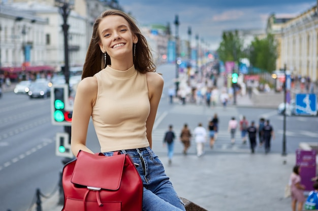 웃고 있는 날씬한 유럽 여성이 저녁에 도시 거리에서 쉬고 있다
