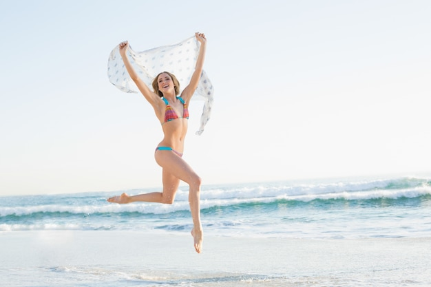 목도리를 들고 공중에 점프 웃는 날씬한 여자