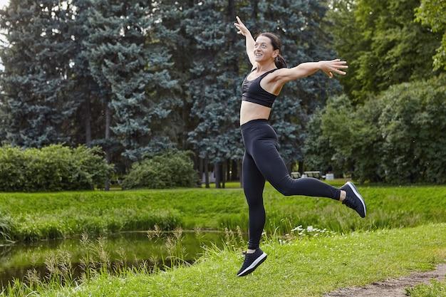 웃는 슬림 활성 여자는 공공 공원에서 야외에서 신체 운동을하고 있습니다.