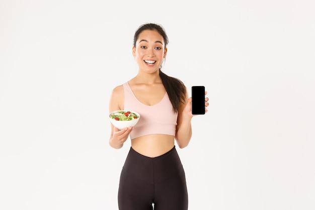 Улыбающаяся стройная и симпатичная азиатская фитнес-девушка, тренер спортзала показывает салат и экран смартфона, рекомендую скачать трекер диеты или напоминание о калориях.