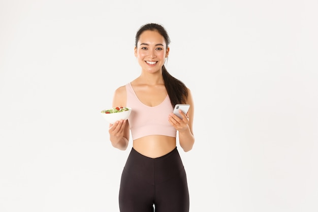 Smiling slim asian fitness girl in sportswear, holding salad and mobile phone, using eating reminder app, diet control application, checking calories.