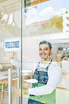 Smiling small bakery owner stocking welcome sign on glass door when opening cafe in the morning