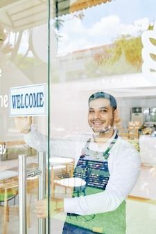 Улыбающийся владелец небольшой пекарни держит приветственный знак на стеклянной двери при открытии утреннего кафе