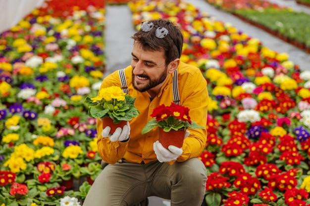 Улыбающийся владелец малого бизнеса сидит в теплице и держит порты с яркими цветами