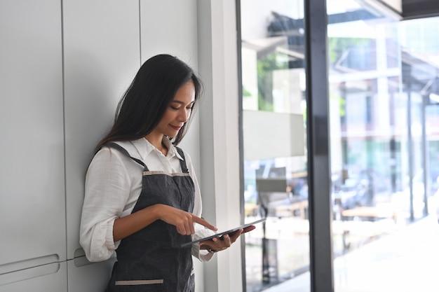 Улыбающийся владелец малого бизнеса, стоящий в своей кофейне и использующий цифровой планшет