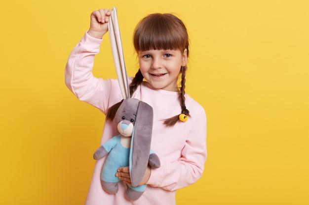 Улыбающийся маленький ребенок женского пола тянет пушистого кролика к ушам и смотрит в камеру с счастливым выражением лица, ребенок в бледно-розовой рубашке позирует изолированным на желтом фоне.