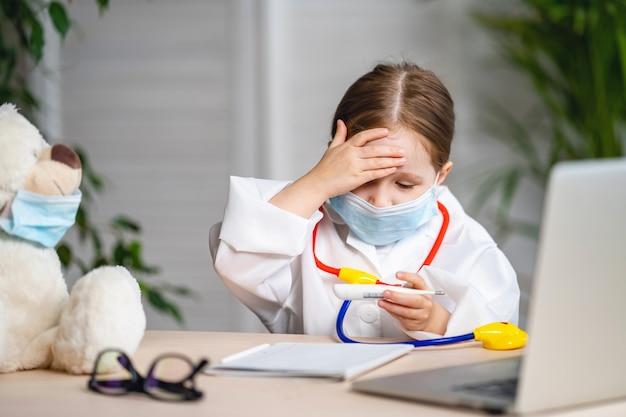 Улыбаясь маленькая девочка носить белые пальто и маску, измеряется температура плюшевого мишку.