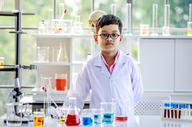 Smiling smart asian boy in glasses and white lab coat standing at desk with flasks with colorful liquids and looking at camera during chemistry lesson in school laboratory
