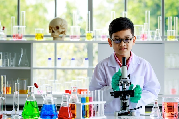Smiling smart asian boy in glasses and white lab coat standing at desk with microscope and flasks with colorful liquids and looking at camera during chemistry lesson in school laboratory.