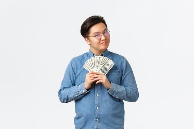 웃는 스마트 아시아 남성 기업가, 돈을 들고 만족 찾고 안경에 프리랜서