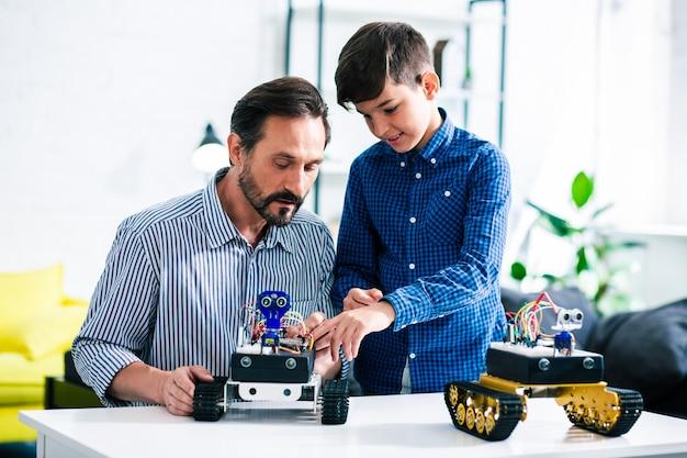 自宅で息子と一緒に休んでいる間、ロボットデバイスを見せて笑顔のスマートな男の子