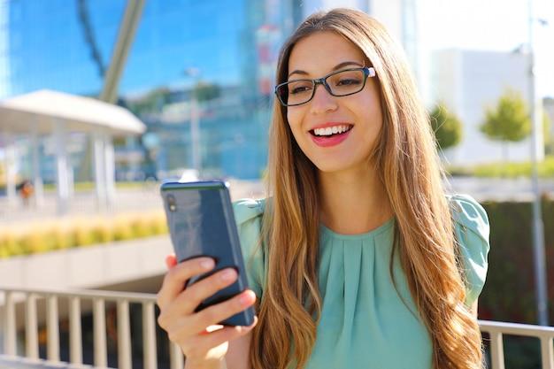 バックグラウンドでのオフィスビルが付いている通りで携帯電話を持つスマートビジネス女性の笑みを浮かべてください。