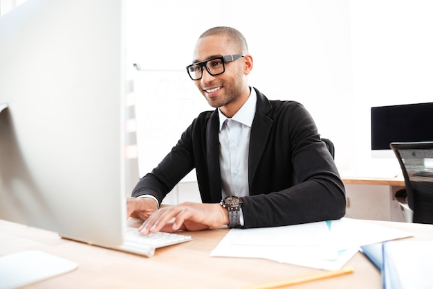 Smiling smart businessman working with computer at the office