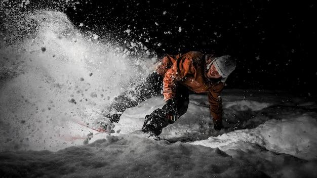 Улыбающийся сноубордист в оранжевой куртке верхом на снежном холме ночью