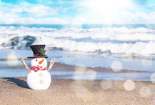 太陽が降り注ぐビーチで笑顔の雪だるま。メリークリスマスと幸せな新年のカードの休日の概念