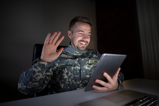 Smiling soldier in military uniform getting reunited with his family via tablet computer
