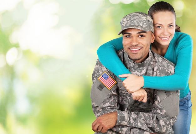 배경에 서 있는 그의 아내와 함께 웃는 군인