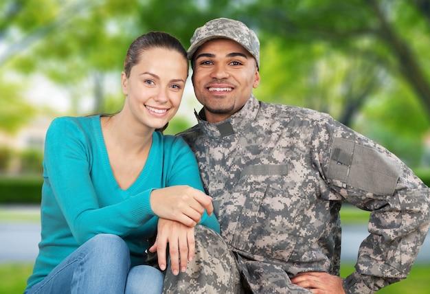背景に立っている彼の妻と笑顔の兵士