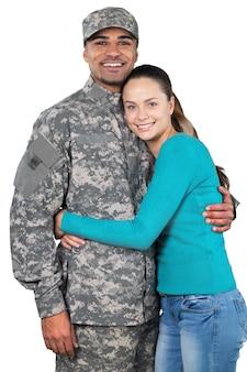 흰색 배경에 서 있는 그의 아내와 함께 웃는 군인