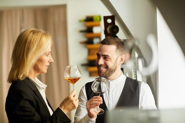 Smiling sommeliers tasting wine