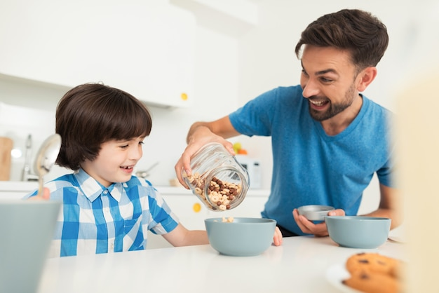 Smiling son and father have breakfast in kitchen.