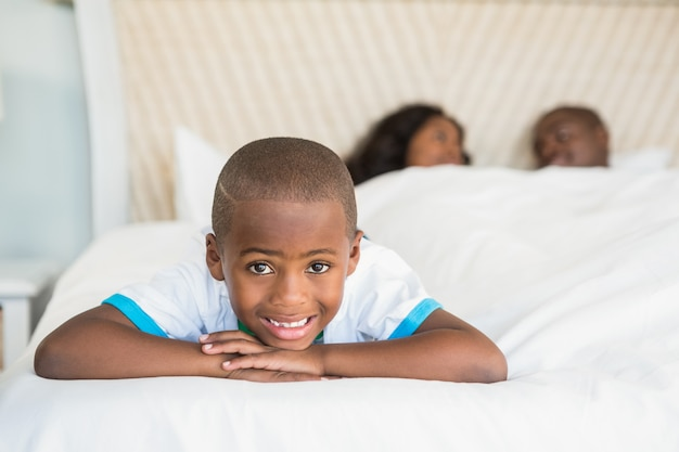 Smiling son lying on bed
