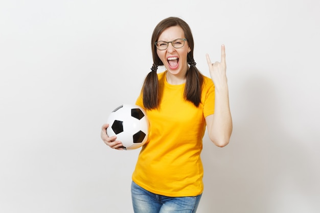 Smiling sport european woman, two fun pony tails, football fan or player in glasses, yellow uniform, depict heavy metal rock sign, horns gesture, hold classic soccer ball isolated on white background.