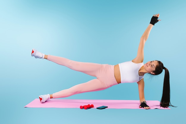 Smiling sportive brunette doing exercises for the whole muscle group on a fitness mat on a blue