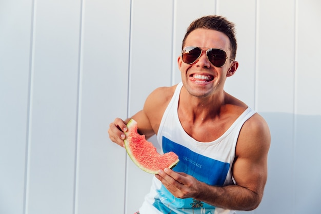 Smiling sportive man with watermelon, enjoying eating, looking at camera