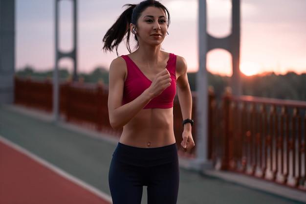 ワイヤレスヘッドフォンで音楽を聴きながら、朝の歩道を走っている陽気な若い女性の笑顔