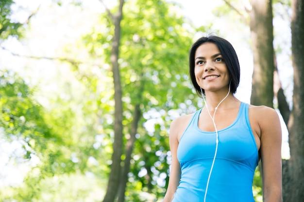 Улыбающаяся спортивная женщина в наушниках на открытом воздухе