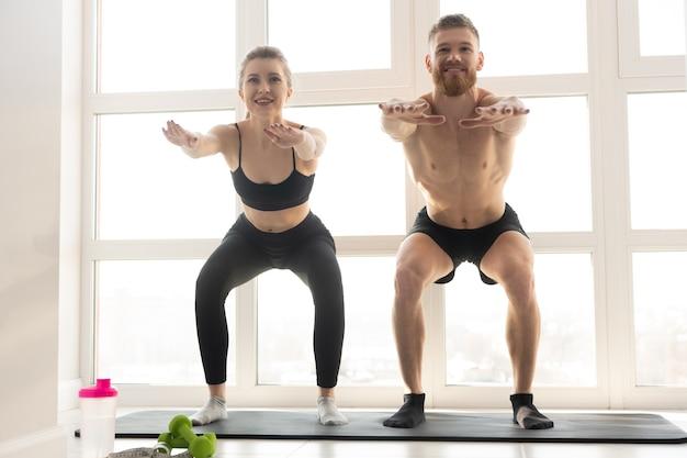 웃는 운동가와 운동가는 피트 니스 매트에 앉는다. 금발의 여자는 운동복을 입는다. 벌거 벗은 몸통을 가진 수염 난 남자. 집에서 스포츠 활동의 개념입니다. 현대적인 넓은 햇볕이 잘 드는 아파트의 인테리어